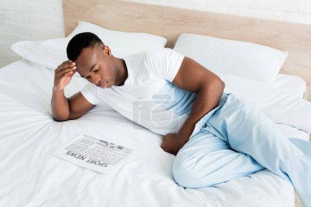 Photo pour Vue d'angle élevé du journal de lecture d'homme américain africain calme, se trouvant sur le lit - image libre de droit