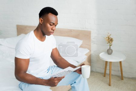 Photo pour Calme homme américain africain assis sur le lit, journal de lecture, tenant tasse avec la boisson dans la main - image libre de droit