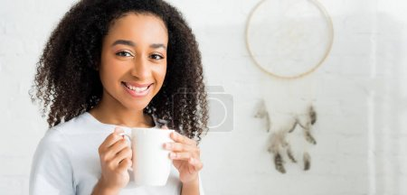 Photo for Happy african american woman holding cup in hands, looking at camera - Royalty Free Image