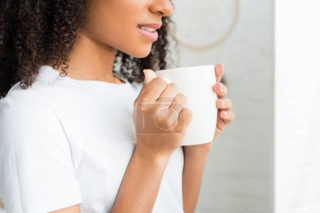 Photo for Cropped view of calm african american woman with white cup in hands - Royalty Free Image