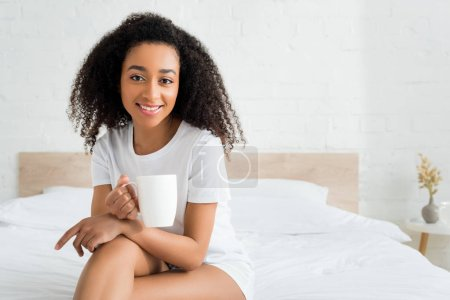 happy african american woman sitting with cup on bed in room