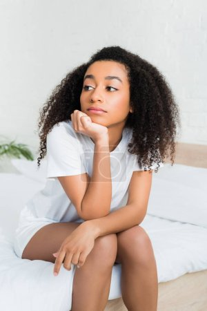 Photo for Calm african american woman sitting on bed, looking away - Royalty Free Image