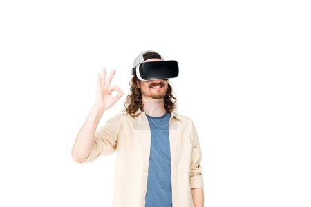 Photo for Young man with VR headset showing Ok sign at camera isolated on white - Royalty Free Image