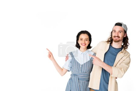 Foto de Young couple pointing with fingers, hugging and looking at camera isolated on white - Imagen libre de derechos