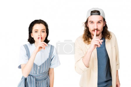 young man and girl showing hush signs at camera isolated on white
