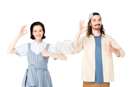 Photo pour Jeune homme et jeune fille montrant les pouces levés et des signes Ok à la caméra isolés sur blanc - image libre de droit