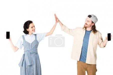 Photo pour Deux personnes tenant smartphones dans les mains et donnant haut cinq isolés sur le blanc - image libre de droit