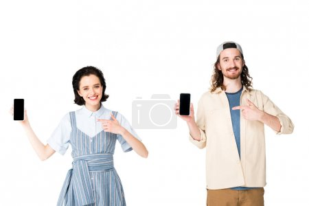 Photo pour Young couple holding smartphones in hands and pointing with fingers at phones isolated on white - image libre de droit
