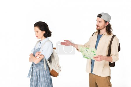 Photo pour Young man holding map in hands, trying to talk to offended girl isolated on white - image libre de droit