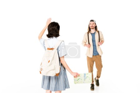 Photo for Full length view of young man walking to girl, who waiving her hand and holding map isolated on white - Royalty Free Image