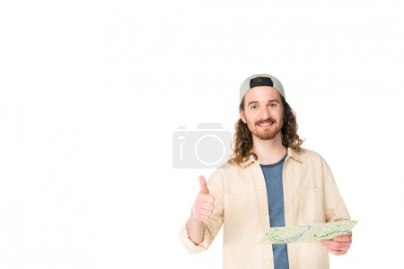 Photo for Front view of young man smilling at camera, holding map and showing thumb up isolated on white - Royalty Free Image