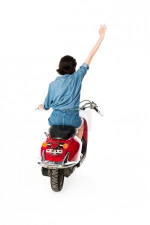 Photo pour Vue arrière de la fille avec la main dans l'air se reposant sur le scooter rouge d'isolement sur le blanc - image libre de droit