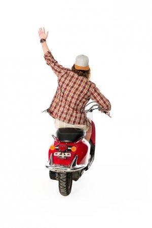 Photo pour Vue arrière du jeune homme avec la main dans l'air assis sur scooter rouge isolé sur blanc - image libre de droit