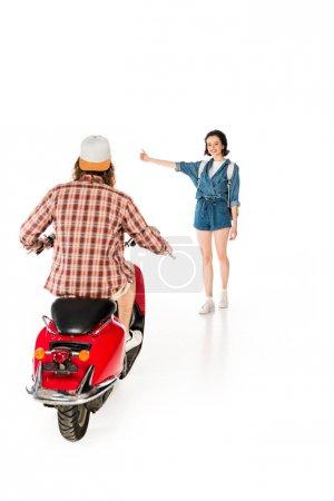 Photo pour Vue pleine longueur de la main tendue de fille et arrêtant le jeune homme s'asseyant sur le scooter rouge d'isolement sur le blanc - image libre de droit