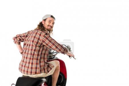 Foto de Hombre joven mirando a la cámara mientras monta en scooter rojo aislado en blanco. - Imagen libre de derechos