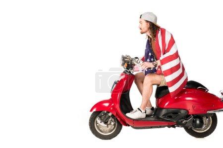 Photo pour Vue de côté de jeune homme avec l'indicateur de l'Amérique s'asseyant sur le scooter rouge d'isolement sur le blanc - image libre de droit