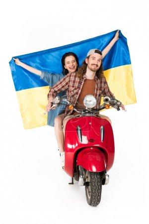 Photo pour Vue pleine longueur de la fille assise sur scooter rouge et tenant drapeau Ukranian et jeune homme regardant vers l'avant isolé sur blanc - image libre de droit