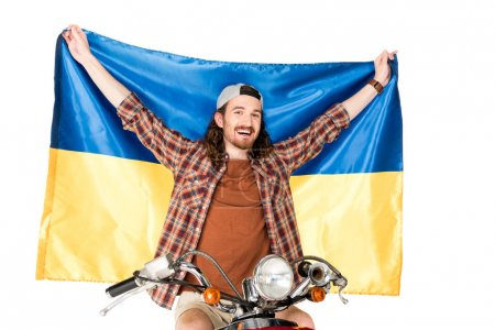 Photo pour Young man sitting on red scooter, holding Ukrainian flag in air isolated on white - image libre de droit