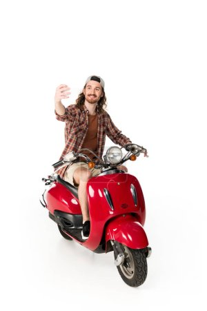 Photo pour Full length view of young man sitting on red scooter and taking selfie isolated on white - image libre de droit