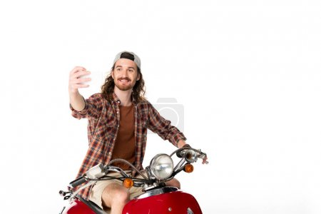 Photo pour Young man sitting on red scooter and taking selfie isolated on white - image libre de droit