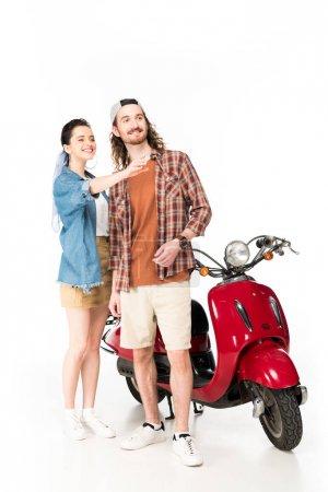 Photo pour Belle fille pointant avec la main et le jeune homme regardant loin, restant près du scooter rouge d'isolement sur le blanc - image libre de droit