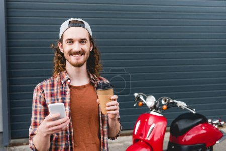 Photo pour Young man holding paper cup with coffee and smartphone, standing near red scooter - image libre de droit