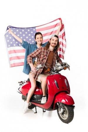 Photo pour Vue pleine longueur de belle fille et jeune homme s'asseyant sur le scooter rouge et retenant le drapeau américain d'isolement sur le blanc - image libre de droit