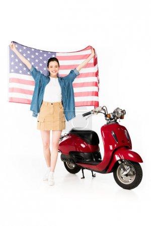 Photo pour Vue pleine longueur de belle fille restant près du scooter rouge et retenant le drapeau américain d'isolement sur le blanc - image libre de droit