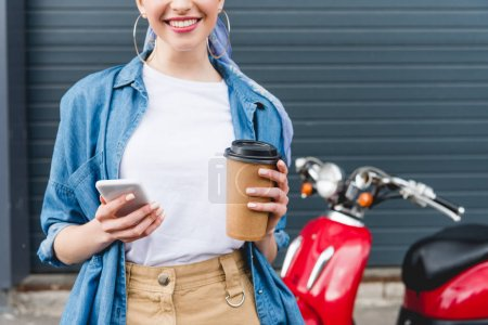 Photo for Cropped view of beautiful girl standing near red scooter, holding paper cup with coffee and smartphone - Royalty Free Image