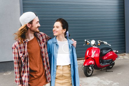 Photo for Young man and girl standing near red scooter and hugging - Royalty Free Image