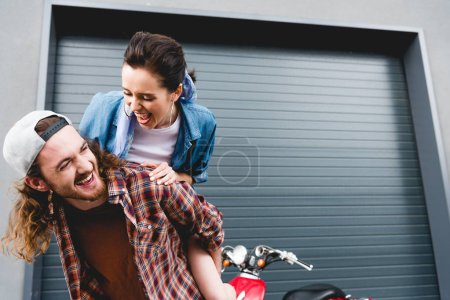 Photo for Young man and girl laughing, piggybacking while standing near red scooter - Royalty Free Image