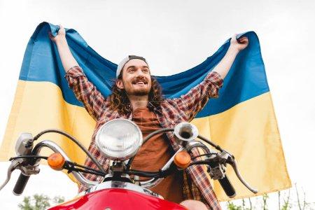 Photo pour Vue bas d'angle de jeune homme s'asseyant sur le scooter rouge et retenant le drapeau ukrainien - image libre de droit