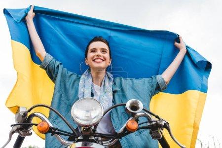 Photo pour Vue à angle bas de belle fille assise sur scooter, souriant et tenant drapeau ukrainien - image libre de droit