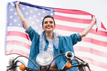 Photo for Low angle view of beautiful girl sitting on scooter, holding American flag and smiling on sky background - Royalty Free Image