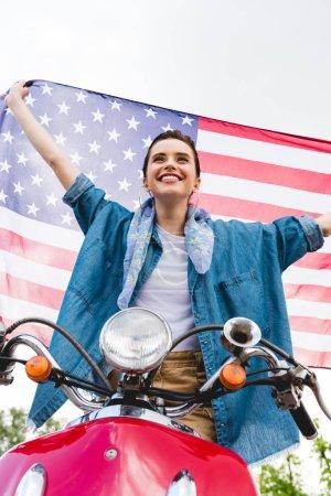 Photo pour Vue basse d'angle de belle fille restant sur le scooter rouge, retenant le drapeau américain et souriant sur le fond de ciel - image libre de droit