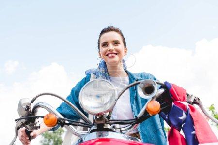 Photo pour Vue bas d'angle de belle fille souriant et conduisant sur le scooter rouge - image libre de droit