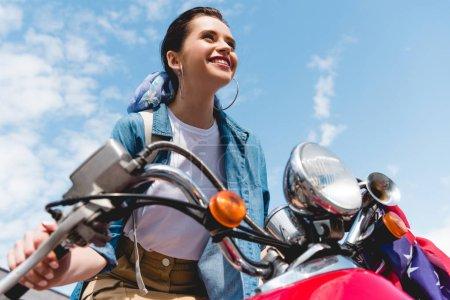 Photo pour Vue basse d'angle de belle fille conduisant sur le scooter rouge, souriant et regardant en avant - image libre de droit