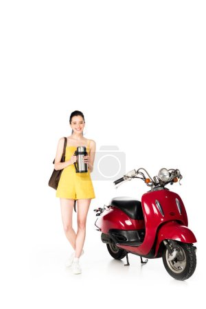 Photo for Full length view of beautiful girl in yellow clothes holding backpack and thermos, looking at camera and standing near red scooter isolated on white - Royalty Free Image