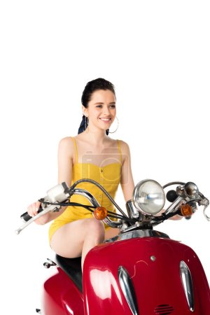 Photo for Beautiful girl sitting on red scooter, looking forward and smiling isolated on white - Royalty Free Image