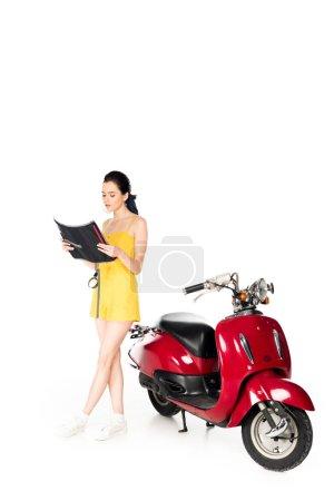 Photo pour Belle fille restant près du scooter rouge et de la carte de fixation d'isolement sur le blanc - image libre de droit