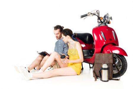Photo pour Un jeune homme et une jeune fille assis sur le plancher près du triporteur rouge et regardant une carte isolée sur du blanc - image libre de droit