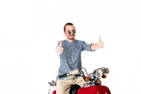 Foto de Guapo joven elegante sentado en scooter rojo y mostrando los pulgares hacia arriba aisladoen en blanco - Imagen libre de derechos
