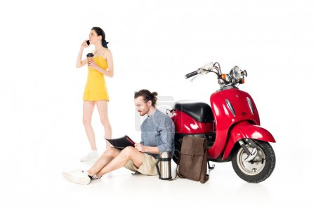 Photo pour Full length view of girl talking on samrtphone, holding paper cup and young man looking at map, sitting near red scooter isolated on white - image libre de droit