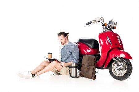 Photo pour Jeune homme retenant la cuvette de papier, regardant la carte et s'asseyant près du scooter rouge d'isolement sur le blanc - image libre de droit