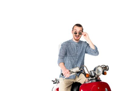 Photo for Handsome stylish, shocked young man sitting on red scooter and looking at camera isolated on white - Royalty Free Image