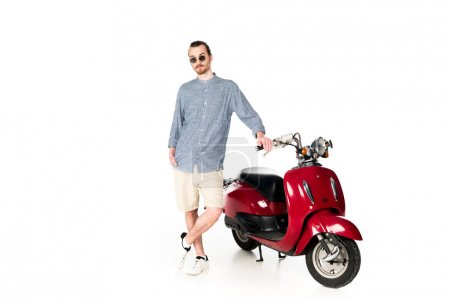 Photo pour Vue pleine longueur de beau jeune homme élégant debout près de scooter rouge et regardant la caméra isolée sur blanc - image libre de droit
