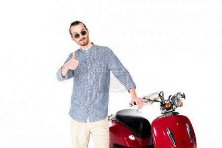 Photo pour Beau jeune homme élégant restant près du scooter rouge, regardant l'appareil-photo et affichant le pouce vers le haut d'isolement sur le blanc - image libre de droit