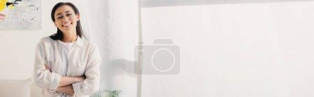 Photo pour Tir panoramique de la femme latine gaie posant à l'appareil-photo avec les bras croisés - image libre de droit