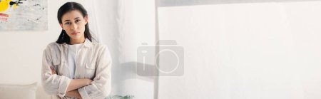 Photo for Panoramic shot of serious latin woman looking at camera while standing with crossed arms - Royalty Free Image