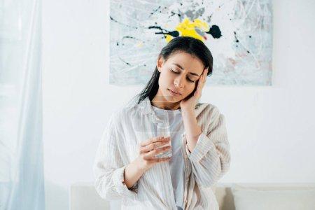 Photo pour Femme latine épuisée avec les yeux fermés retenant le verre de l'eau et touchant la tête avec la main - image libre de droit